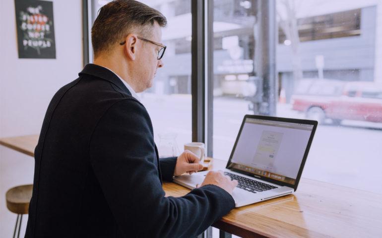 biznesman przed laptopem w kawiarni przegląda wyszukiwarkę b2b